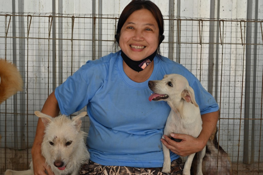 Woman cuddling two dogs
