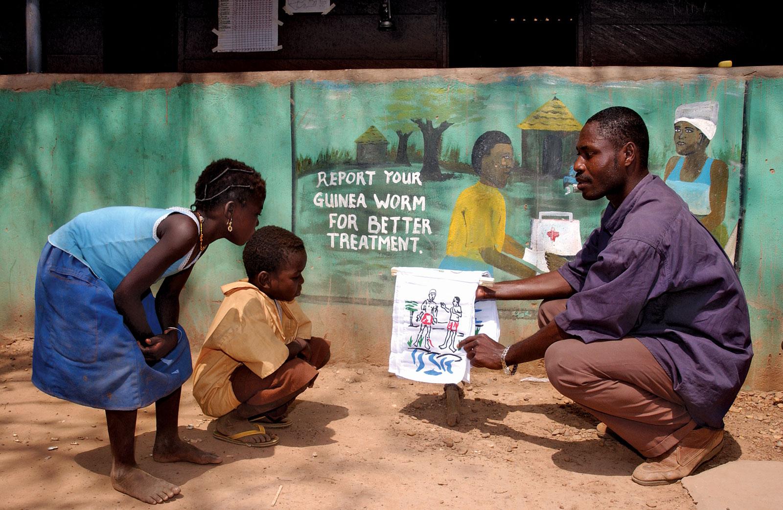 man showing kids info on Guinea Woem